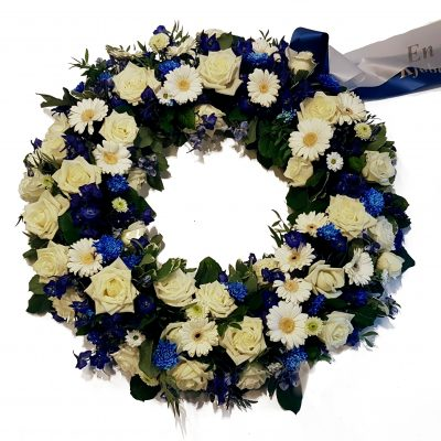 Krans i blå og hvide nuancer. Smuk krans med hvide roser, hvide gerbera, santini hvis chrysantimum