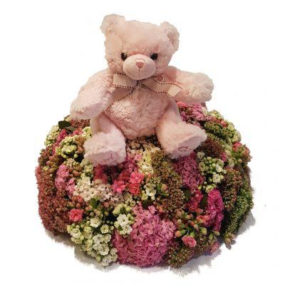 Tæt belagt pude med blomster pyntet med bamse