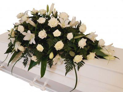 Kistepynt i hvide farver med liljer roser og strå