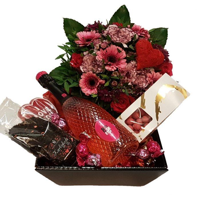 Gavekurv med blomster, mousserende, chokolade med mere