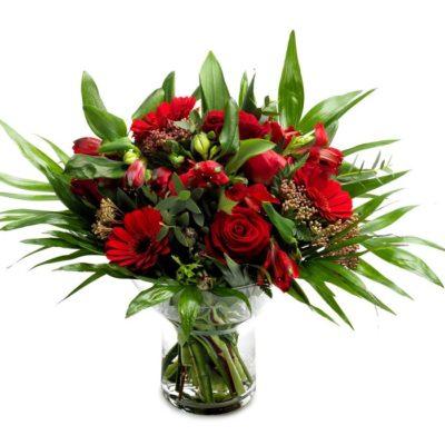Buket i røde farver med roser, alstromeria, gerbera  og andre røde blomster afsluttet med chicco